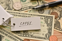 On top of the dollar bills on the table, there is a word book with the financial term CAPEX written on it. It is an abbreviation for Capital expenditure.