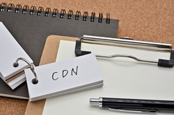 On top of the notebook and clipboard is a wordbook and pen with the word CDN written on it. It means Content Delivery Network.