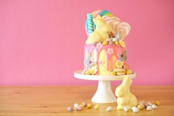 On-trend Easter theme candy land drip cake decorated with lollipops, candy eggs and white chocolate bunny in party table setting.