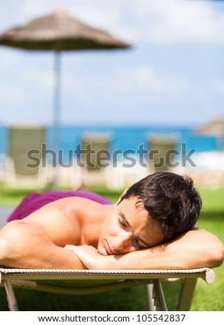 On vacation: young man sunbathing and relaxing on a deckchair near the beach