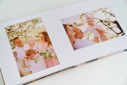 on white background open a photobook from a family photo shoot in the spring garden. Tradition print photo album and review and remember moments of life. services of photographer and designer.