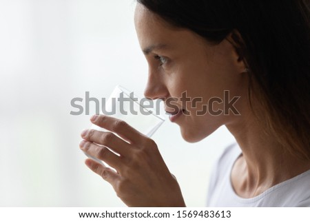 On white grey background 30s woman profile face holds glass of water, copy space for advertisement text or benefits list - helps maintain body fluids balance, keep skin looking good close up concept