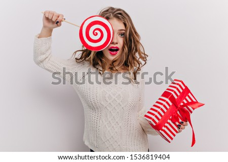 On white isolated background emotional girl with pretty makeup and beautiful manicure, closes one eye with huge caramel candy