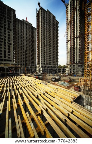 On wood planking between tall buildings under construction and cranes under a blue sky - stock photo
