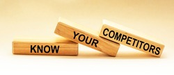 On wooden blocks the text KNOW YOUR COMPETITORS concept of business success.
