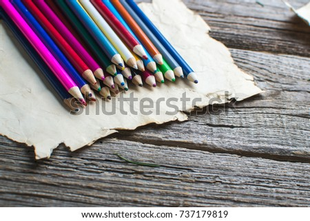 on wooden old table an old sheet, some parchment laid out nicely next to the pencils #737179819