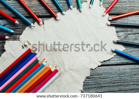 on wooden old table an old sheet, some parchment laid out nicely next to the pencils #737180641