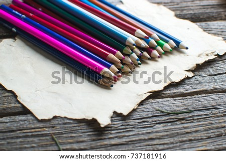 on wooden old table an old sheet, some parchment laid out nicely next to the pencils #737181916