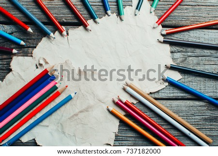 on wooden old table an old sheet, some parchment laid out nicely next to the pencils #737182000