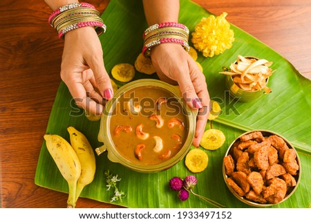 Onam sadhya sweet parippu payasam or dal kheer dessert Kerala, South India. Indian mithai. Women hand serving delicious festival sweet dish for Onam, Vishu, Deepawali, sweet food