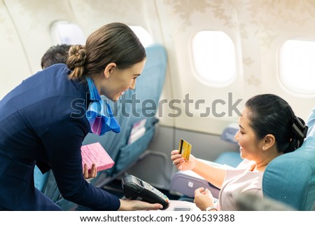 Onboard product purchasing, Asian woman sitting in airplane buying gift from air hostess and paying by credit card tapping on machine. Contactless payment and technology inflight service concept. ストックフォト ©
