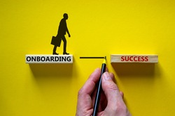 Onboarding success symbol. Wooden blocks with words 'onboarding success'. Businessman hand. Beautiful yellow background, copy space. Business and onboarding success concept.