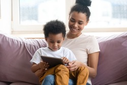 Once upon a time. African millennial mother sitting on sofa at living room holding toddler son on knees watching cartoon on tab pc screen, black nanny teaching little boy to read using education app
