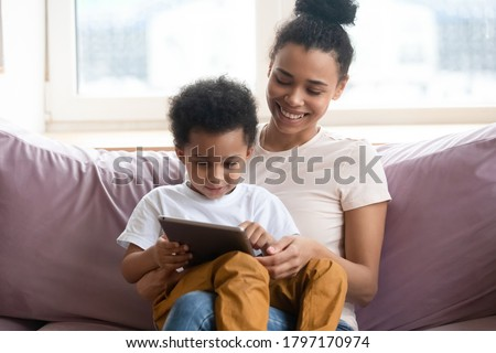 Once upon a time. African millennial mother sitting on sofa at living room holding toddler son on knees watching cartoon on tab pc screen, black nanny teaching little boy to read using education app Сток-фото ©