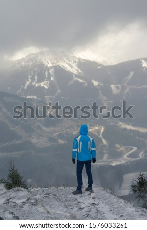 One adult person is hiking in heavy storm with clouds covering the top peak of the mountain Reichenstein, Präbichl in Styria, Austria. He is looking to the sunlight peaking the Leobner Mauer.