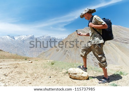 One adult tourist traveller hiker with compass in Himalayas mountains