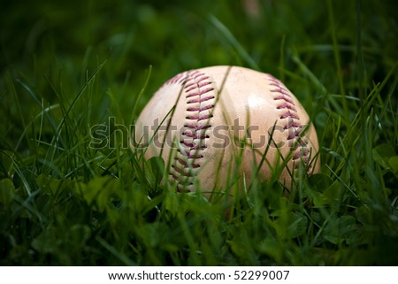 One aged and worn baseball with faded red stitching sits in the green grass. A lost hardball possibly from a homerun hit.
