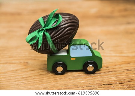 one alone chocolate Easter egg . holiday concept idea with egg on green toy car over wooden table  background. empty copy space for inscription or objects.  #619395890