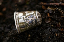 one antique silver thimble with patterns lies on black ground in the street