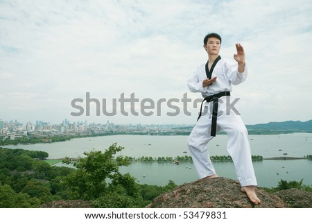 one asian man playing with taekwondo outdoor