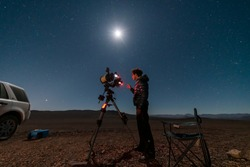 One astronomer man looking the night sky through an amateur telescope and taking photos to the Christmas Star rising over the horizon, an amazing and historical night view at Atacama Desert the Great