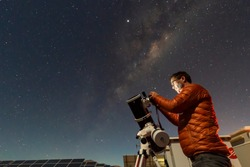 One astronomer man looking the night sky through an amateur telescope and taking photos with the Milky Way rising over the horizon, an amazing night view at Atacama Desert