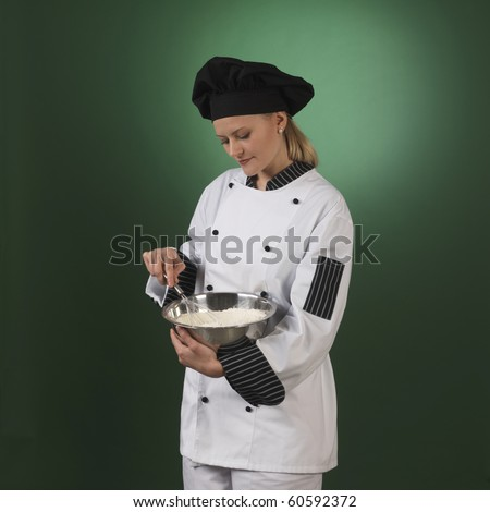 one atractive cook, she is wearing professional uniform and standing stearing a flour bowl. - stock photo