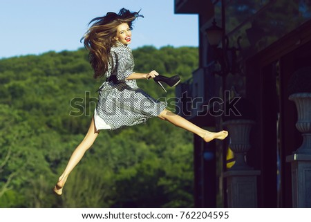 One attractive happy jumping smiling young stylish woman with long hair in black and white blouse holding high heeled shoes sunny day outdoor on natural background, horizontal picture