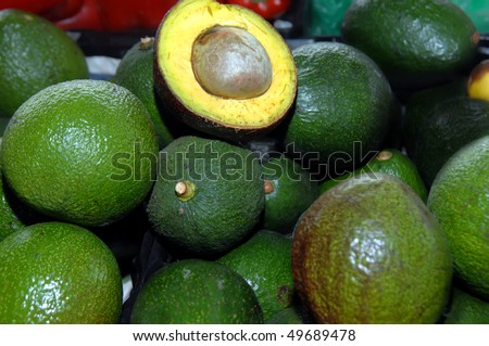 One avocado, in a pile of twenty or more, has been cut in half to show the fruit pulp and seed.