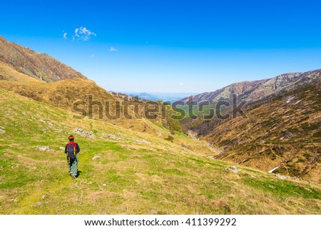 One backpacker hiking uphill on footpath in the italian Alps. Summer adventures and exploration on the Alps. Wide panoramic view from above. #411399292