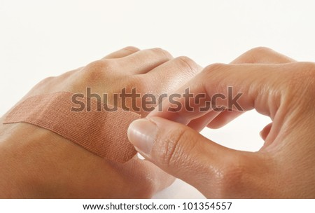 One bare female hand sticking bandaid over cut on the other hand.