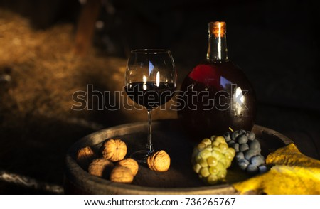 One barrel of wine standing nerar full bottle and full wineglass and yellow flowers #736265767