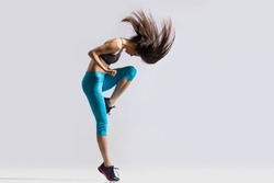 One beautiful young fit modern dancer lady in blue sportswear warming up, working out, dancing with her long hair flying, full length, studio image on gray background