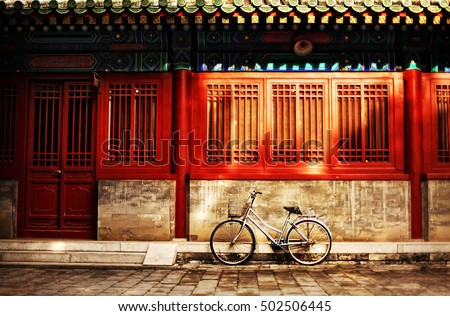 One bicycle in front of oriental red building in urban Asia city on street sidewalk on sunny afternoon