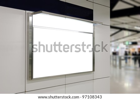 One big horizontal / landscape orientation blank billboard on modern white wall with subway concourse background