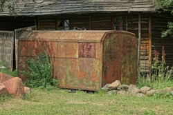 one big old iron trailer in brown rust on the street overgrown with green grass and vegetation