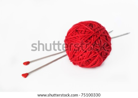 One big red ball of yarn and two long needles for knitting