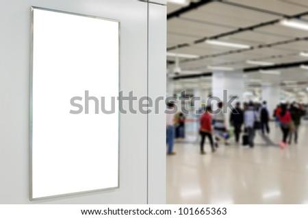 One big vertical / portrait orientation blank billboard on modern white wall with blued passenger background