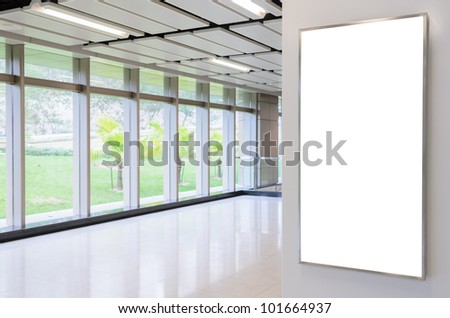 One big vertical / portrait orientation blank billboard on modern white wall with corridor background