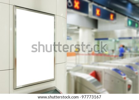 One big vertical / portrait orientation blank billboard on modern white wall with entrance of railway station background
