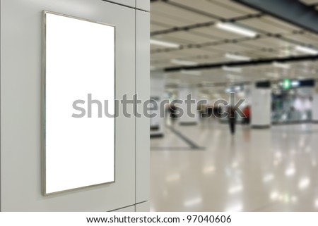 One big vertical / portrait orientation blank billboard on modern white wall with subway concourse background