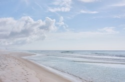 One bird flies low over gentle waves. Quiet and misty winter morning at Panama City Beach... pastel shades