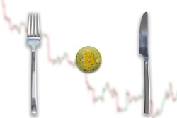 One Bitcoin crypto currency between fork and knife. Concept of Bitcoin scalability problem. Cryptocurrency market deficit and limitations. Blurred trade chart going down background