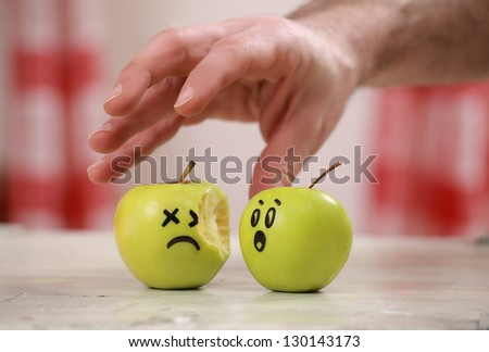 One bitten apple and another one with comic painted face looking worried about the hand from above