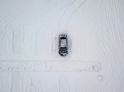 One black car in a snow-covered parking lot. Aerial drone view. Winter snowy morning.