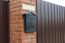 one black iron mailbox on a brown brick wall and a metal fence