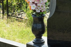 one black marble vase with colored artificial flowers stands at the monument on the grave
