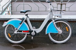One blue rent bicycle stays on the street outdoor. Rental network service. City. Urban. Sustainable. Eco-friendly. Wet weather. Rainy. Rainю. Copy-space for advertising on wings
