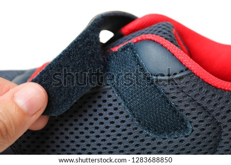 Photo of  One blue sneakers with Velcro fastener isolated on white. Clothe-up. Sport shoes. Side view.
