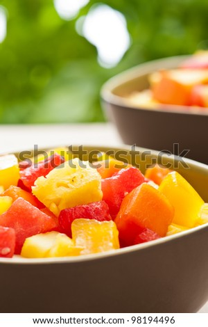 One bowl of Mixed tropical fruit salad in front of nature a background